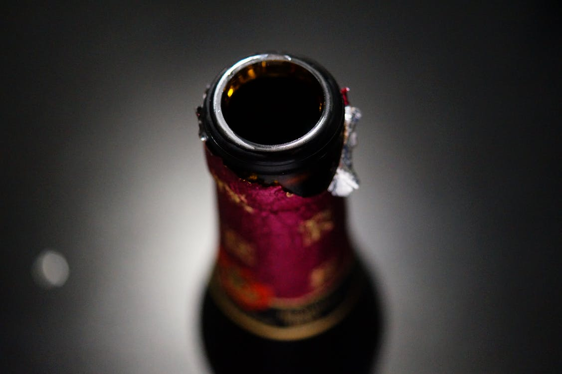 Selective Focus Photography of Amber Glass Bottle Lid