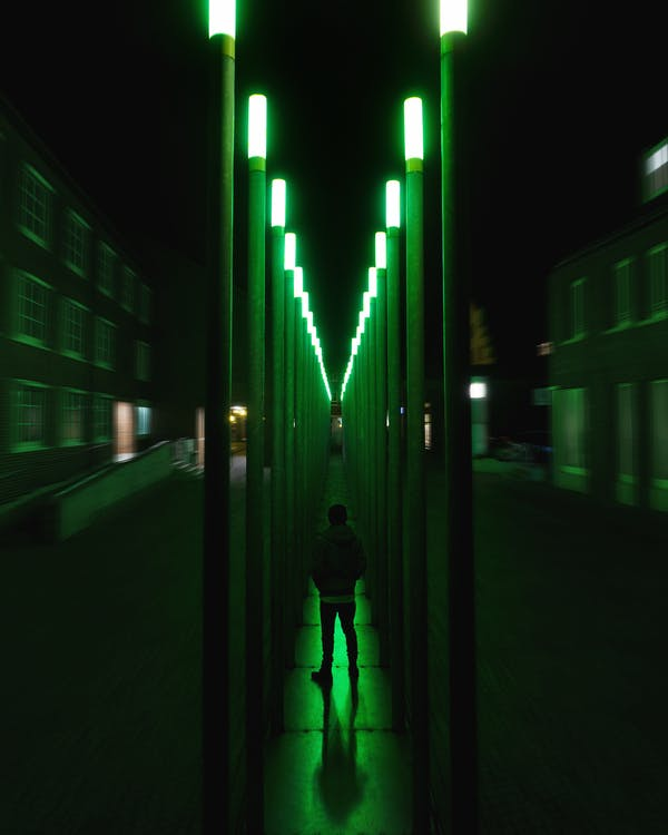 Person Standing On Green Lighted Hallway