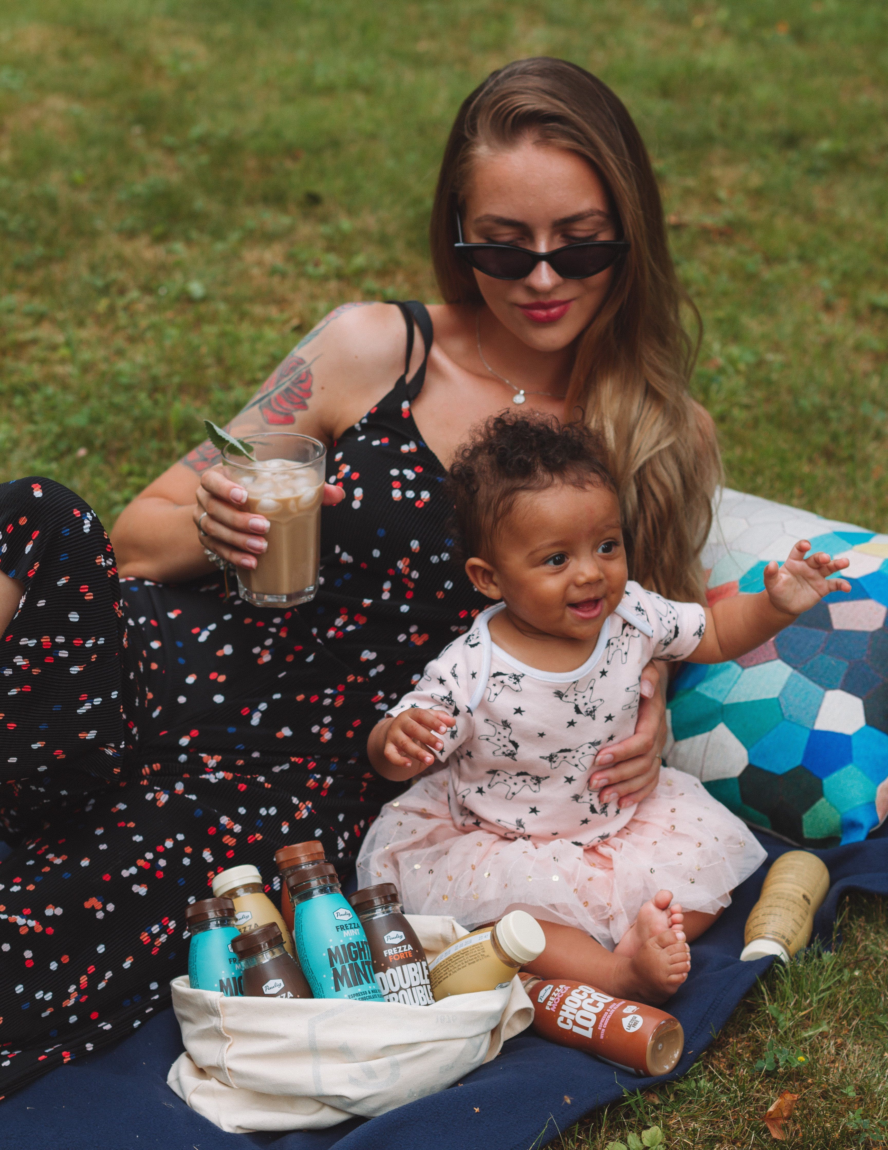 Woman Leaning on Grass While Holding Child and Glass of Drink