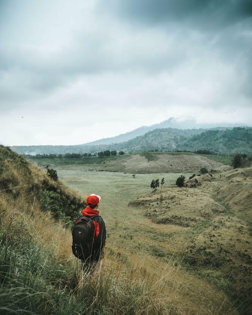 Landscape Photo of Man Facing Brown Mountain