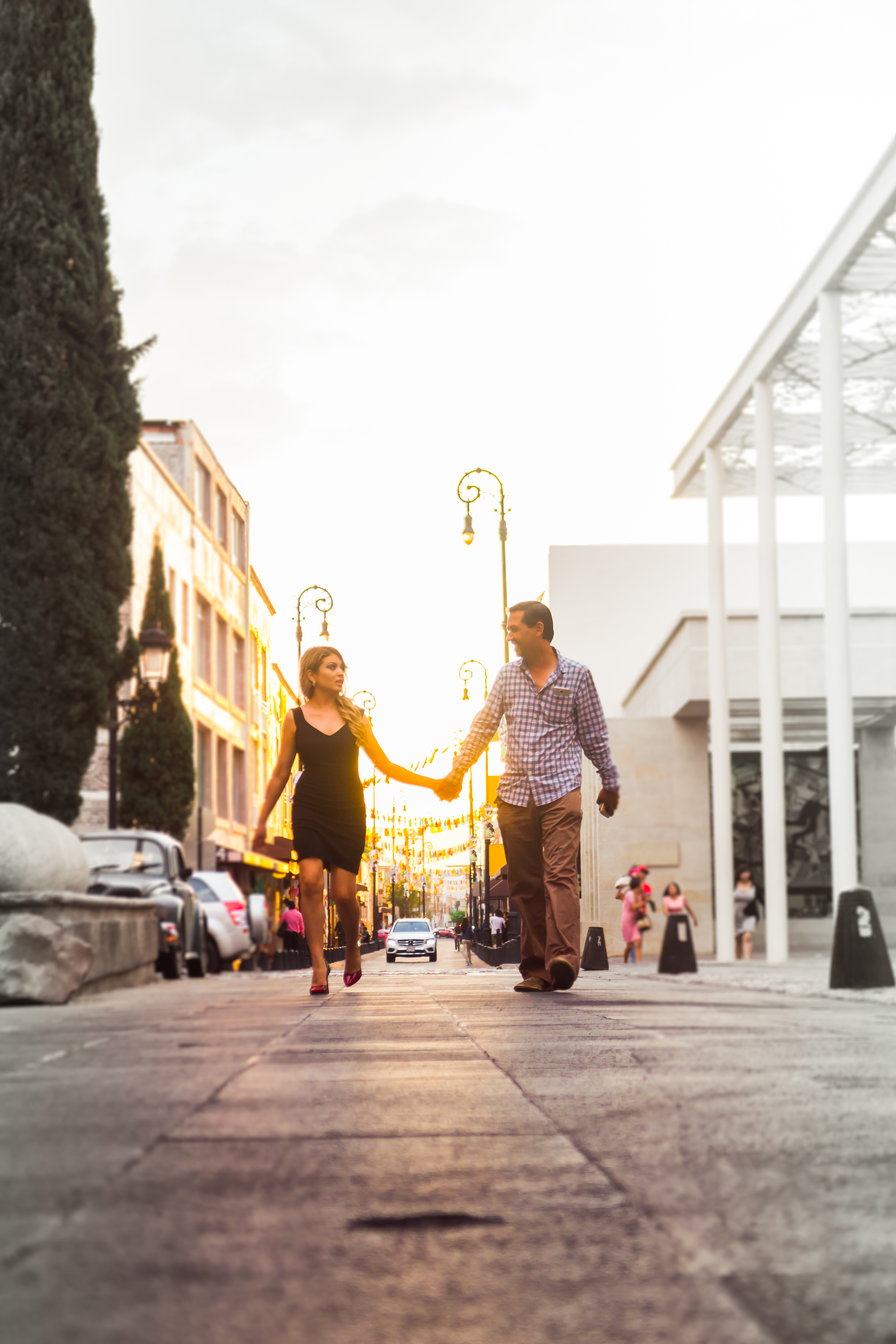 Man and Woman Walking on Street While Holding Hands