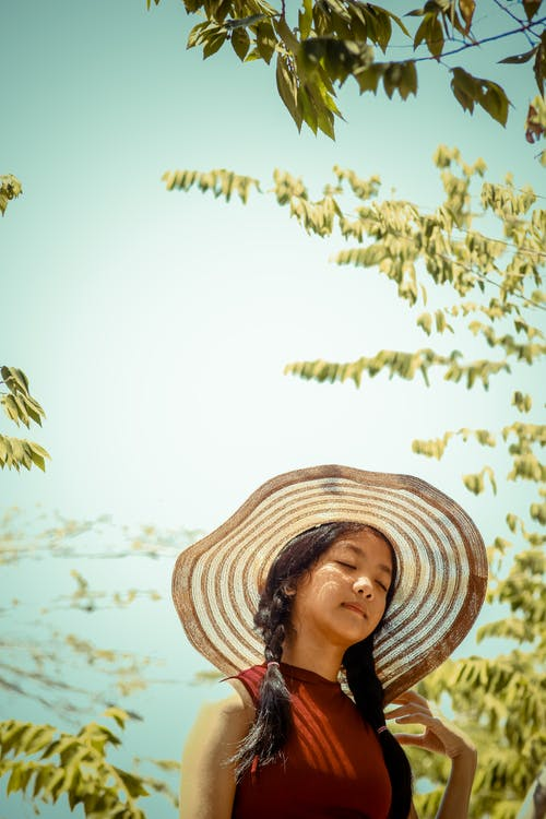 Selective Focus Photography of Woman Wearing Sunhat Near Tree