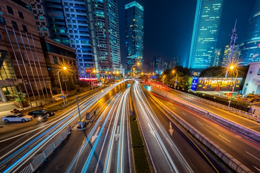 Timelapse Photography of Vehicle on Concrete Road Near in High Rise Building during Nighttime
