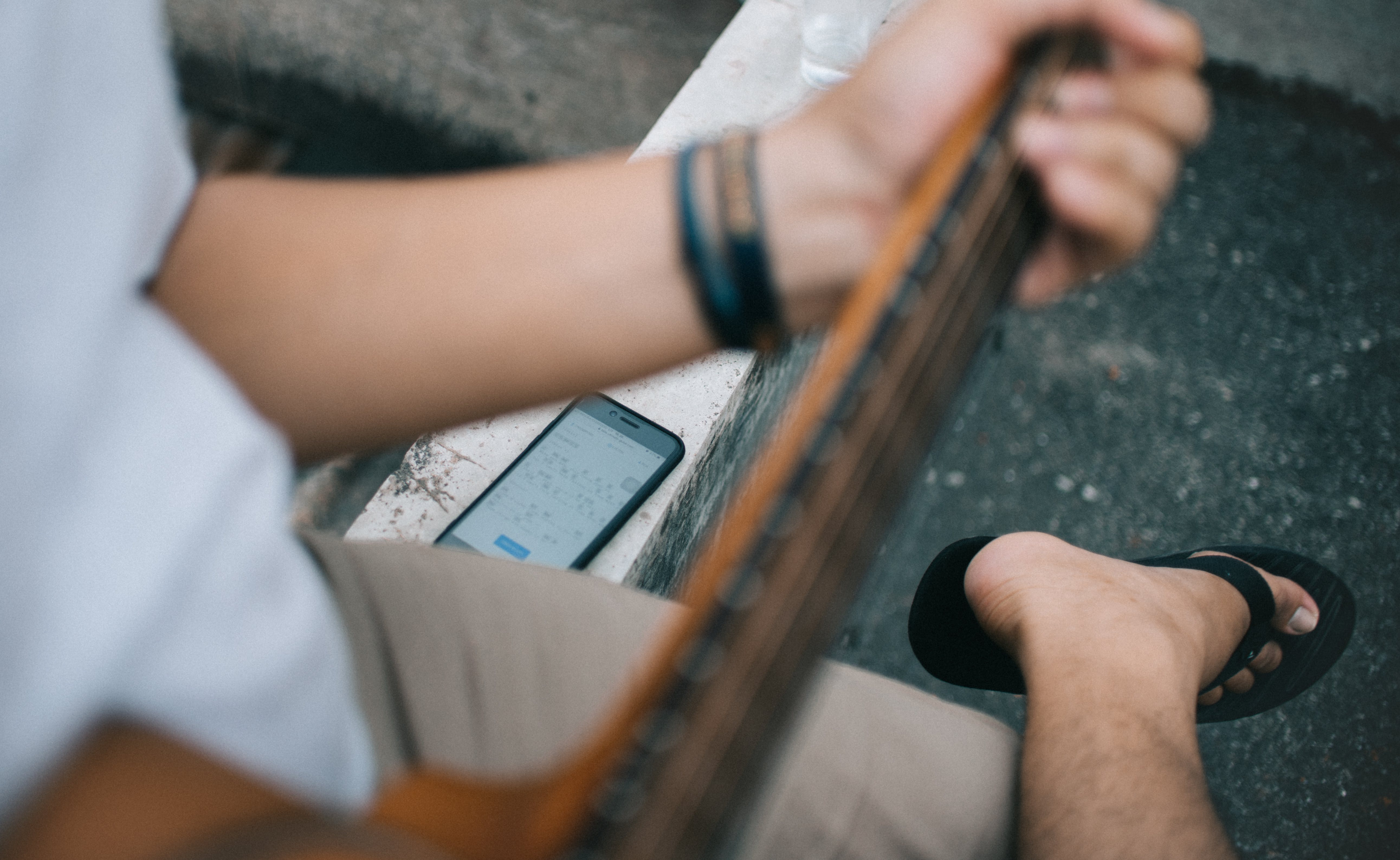 Person Holding Guitar Sitting Beside Black Smartphone