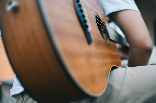 Selective Focus Photo of Man Holding Guitar