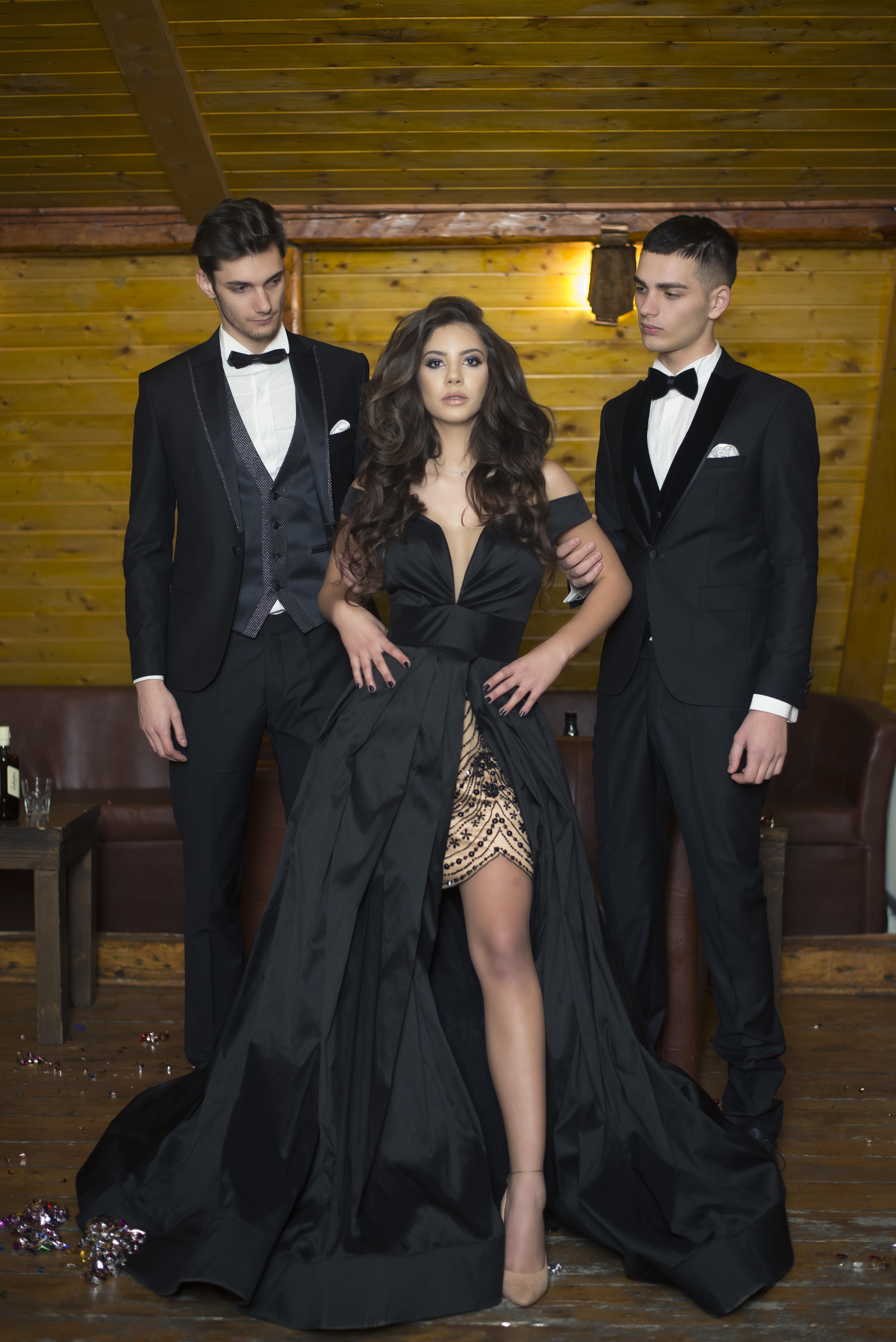 Woman Wearing Black Dress Standing in Between Two Men Wearing Black Suit
