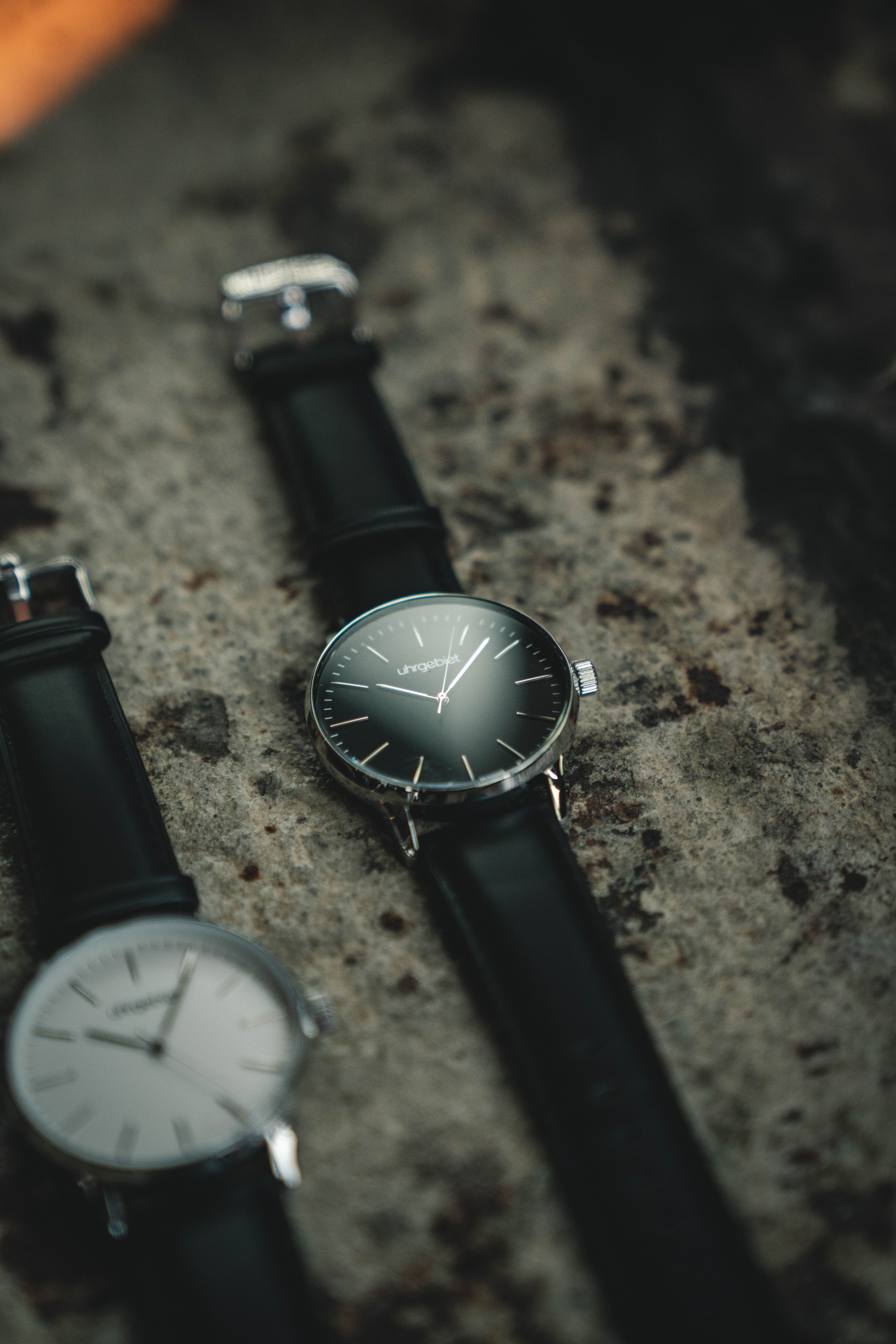 Photo of Two Analog Watches with Black Leather Bands on Gray Surface