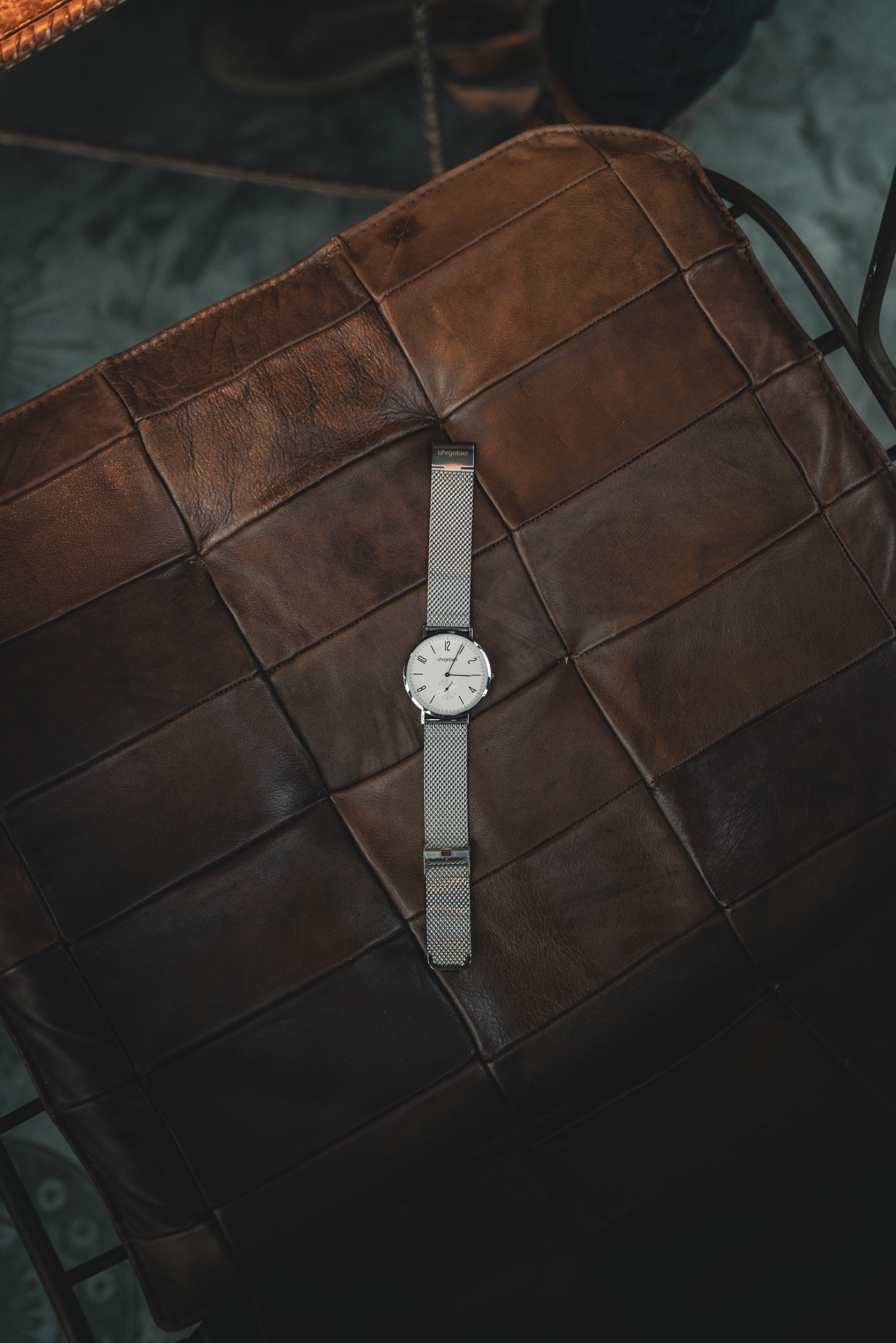 round silver colored watch on table