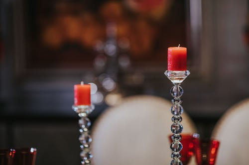 Selective Focus Photography of glass candle holder with red candle