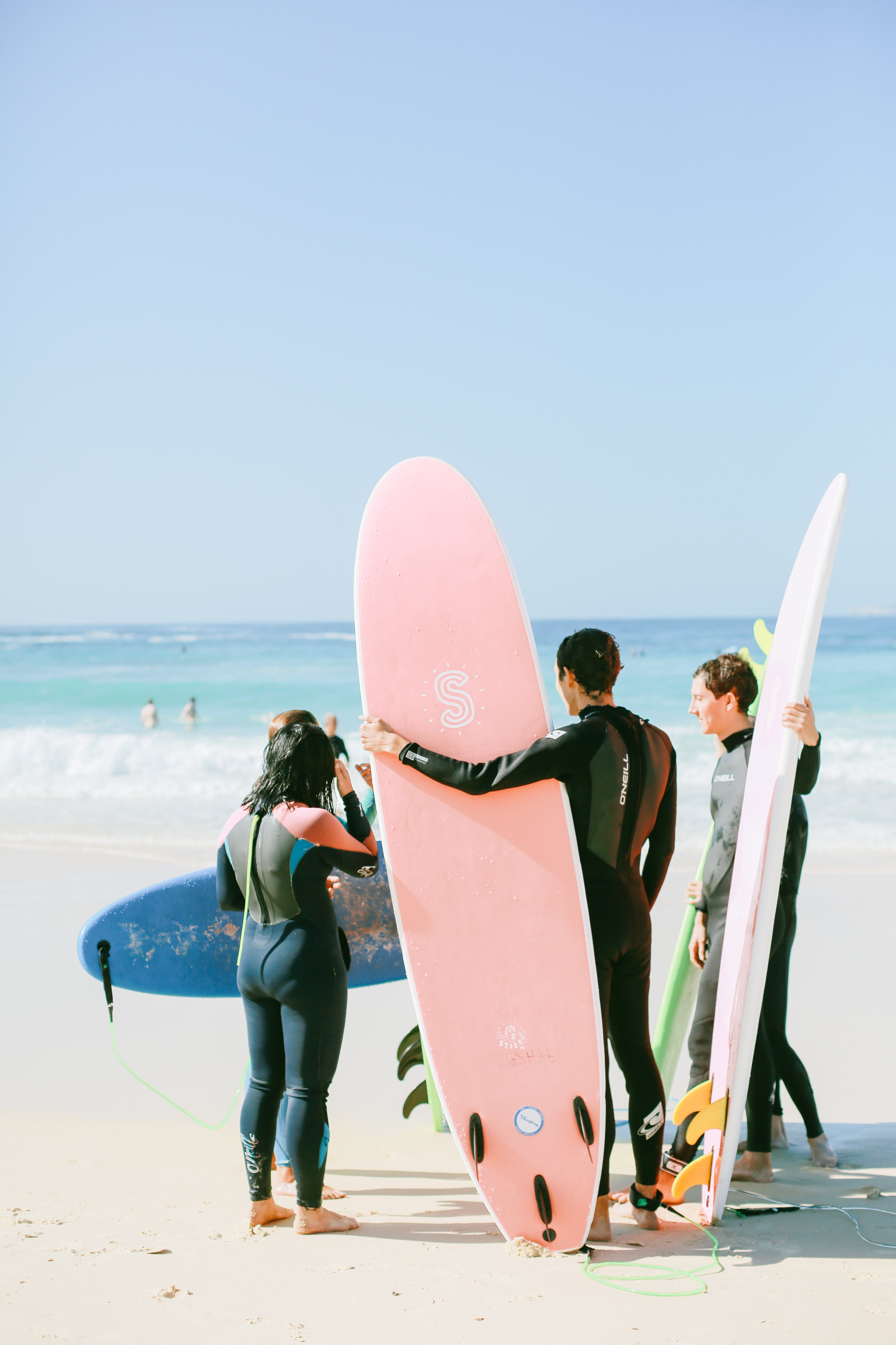 Photo of People Holding Their Surfboards