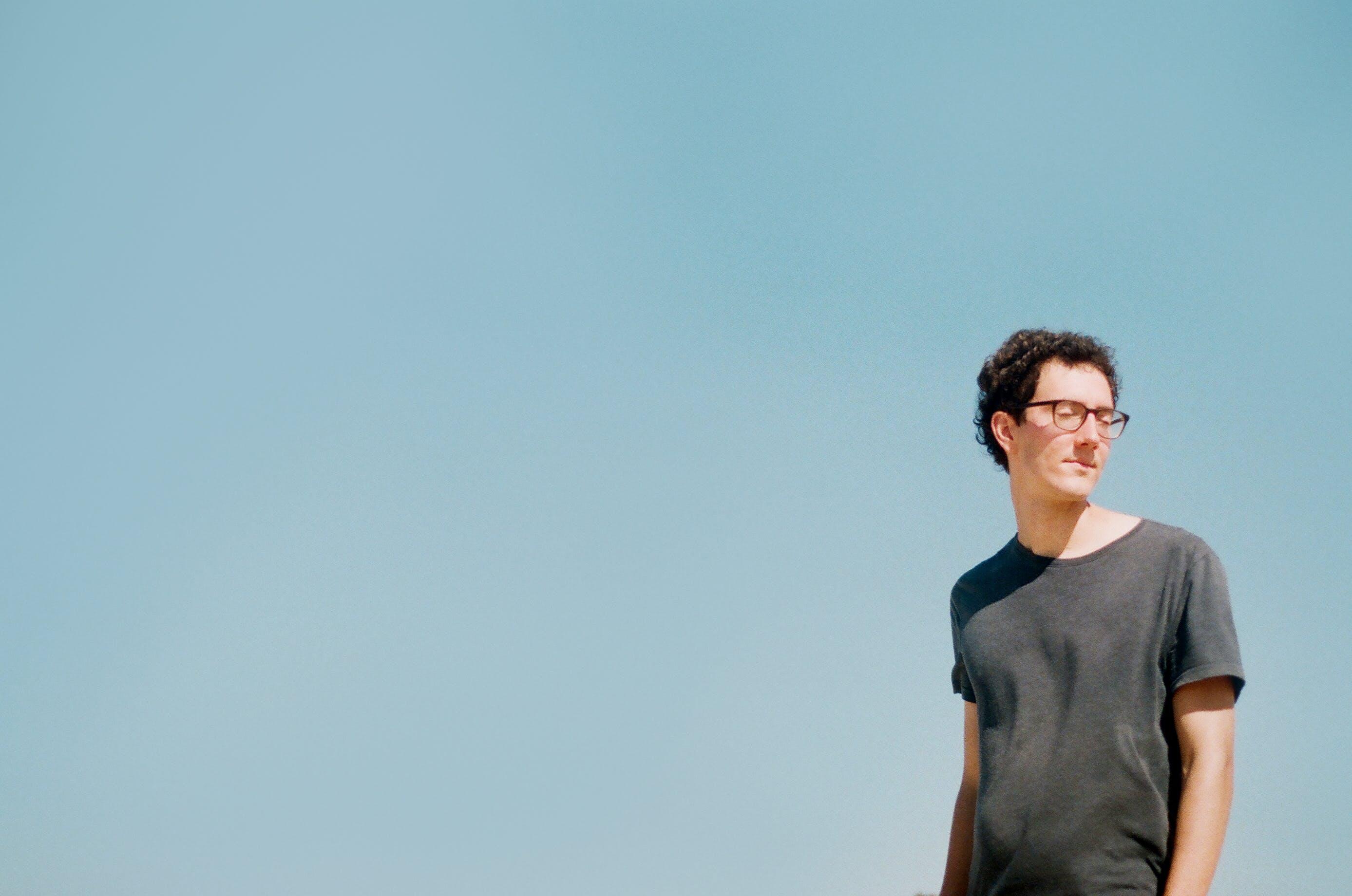 Man Standing Under Blue Sky