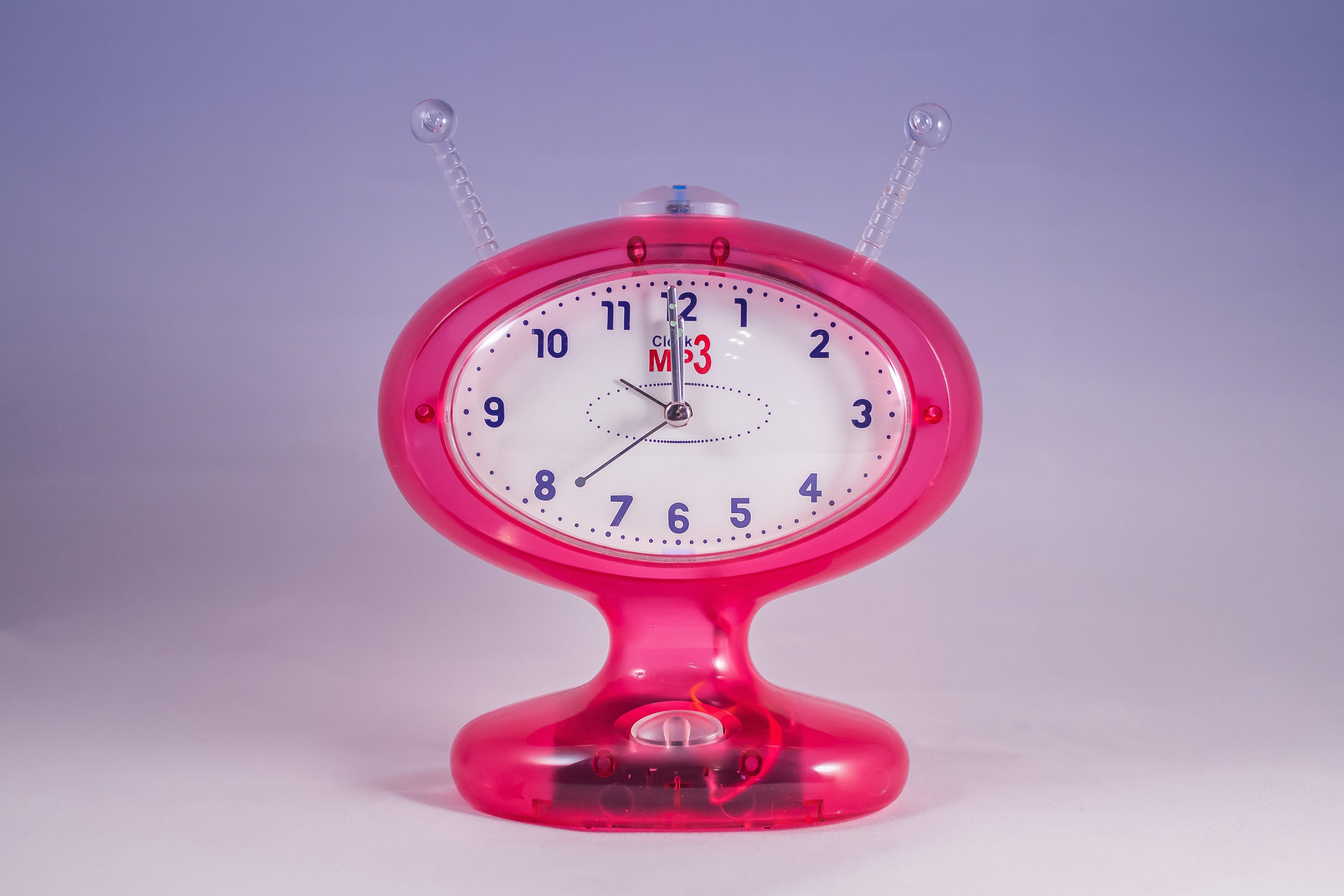 Pink and White Mp3 Analog Clock Displaying at 12:00
