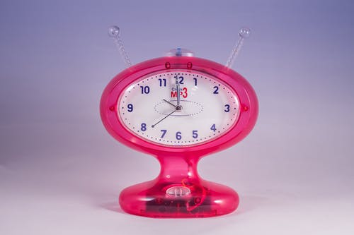 Pink and White Mp3 Analog Clock Displaying at 12:00