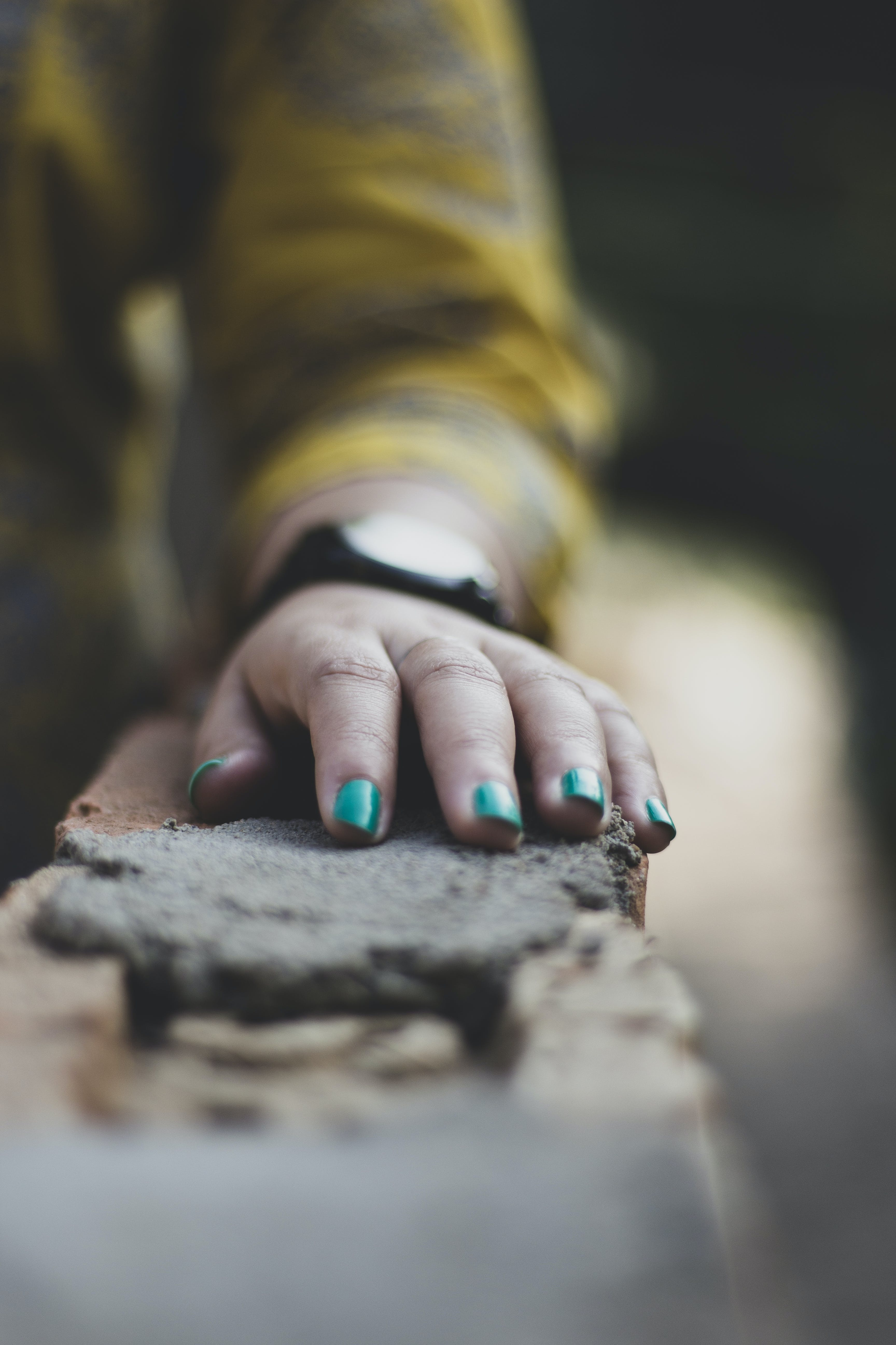 Woman's Hands Resting on Concrete Surface