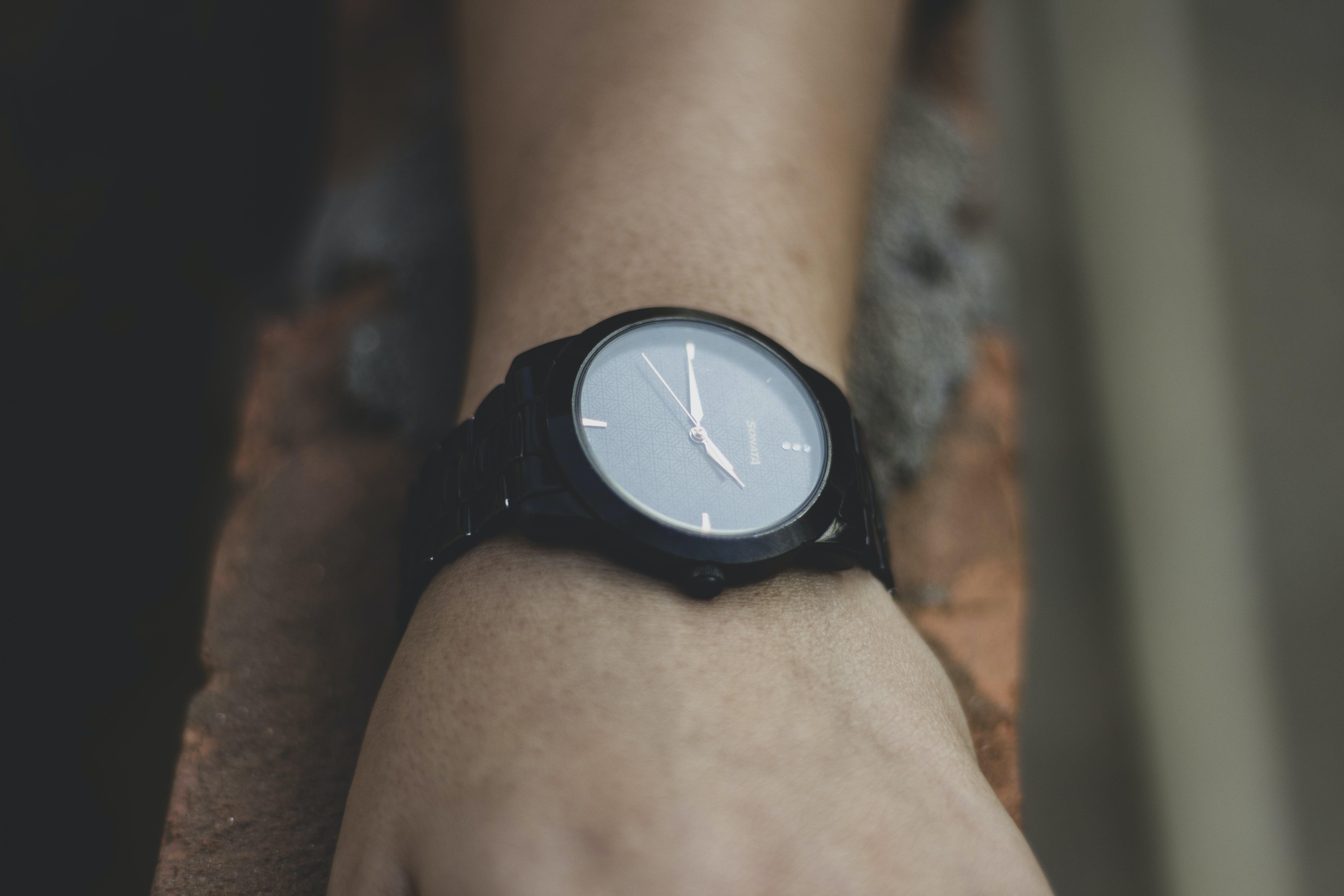 Round Black Analog Watch Displaying 7:15 Time