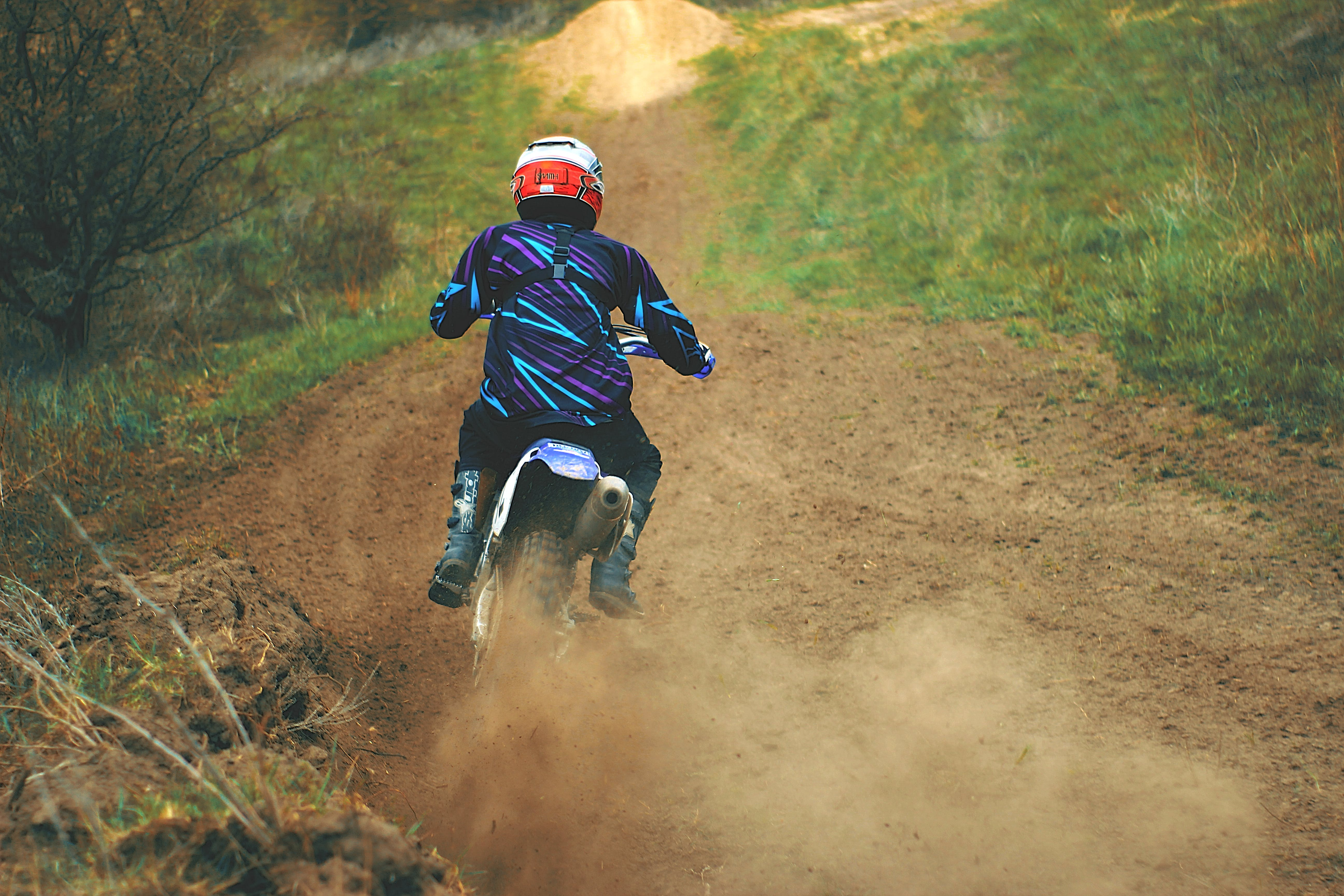 Man Riding Motocross Dirt Bike on Dirt Road