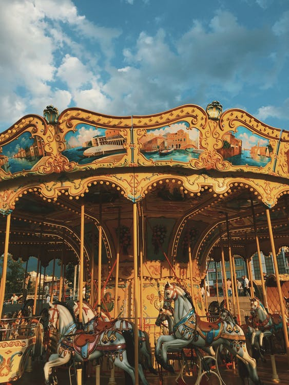 Low angle of round festive carousel horses located in amusement park against cloudy blue sky