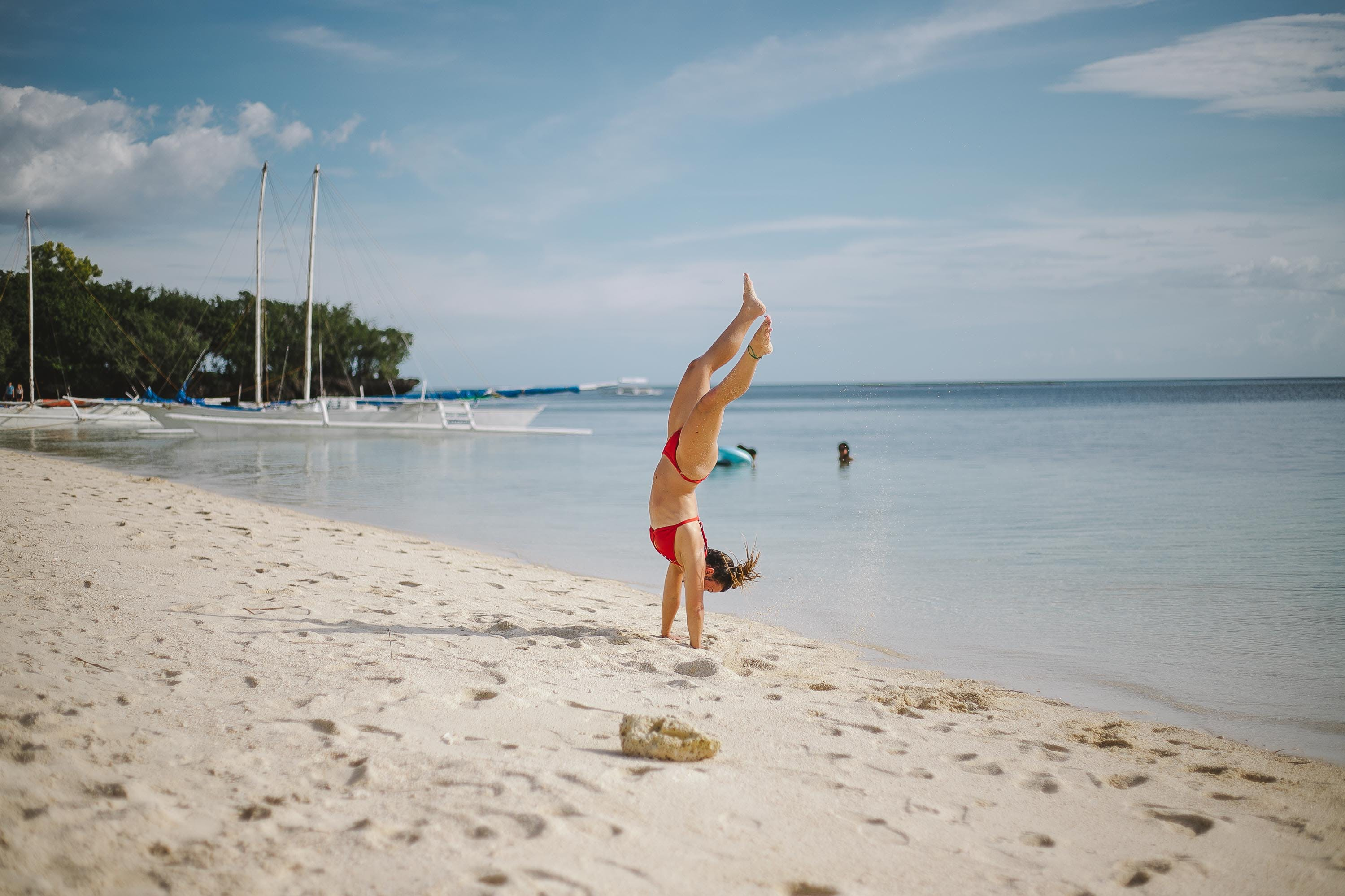 Woman Doing Head Stand on Shoreline