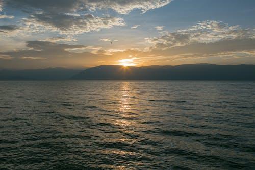 上面點綴著黃色, 日落, 海 的 免費圖庫相片