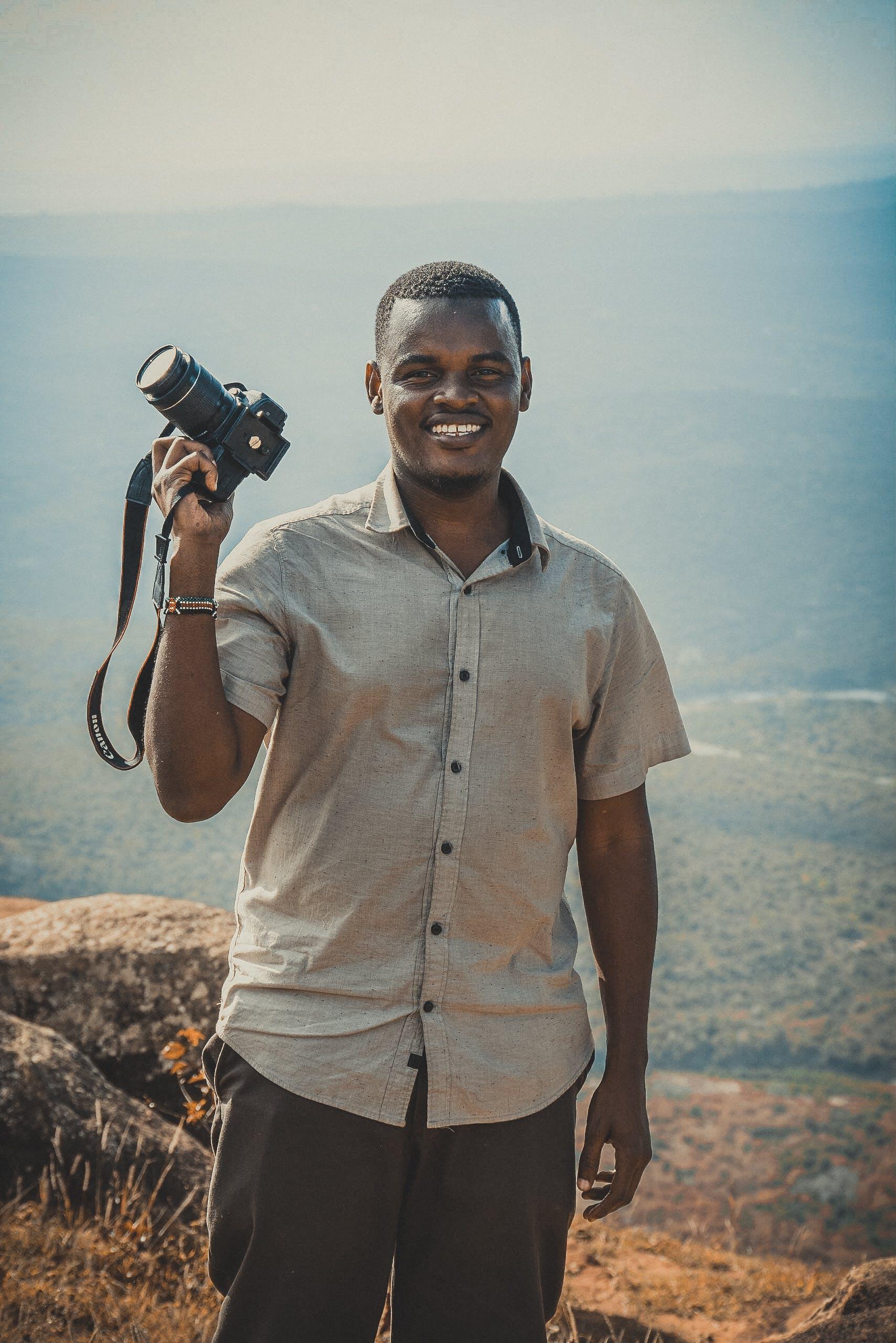 Man Holding Dslr Camera Standing on Cliff
