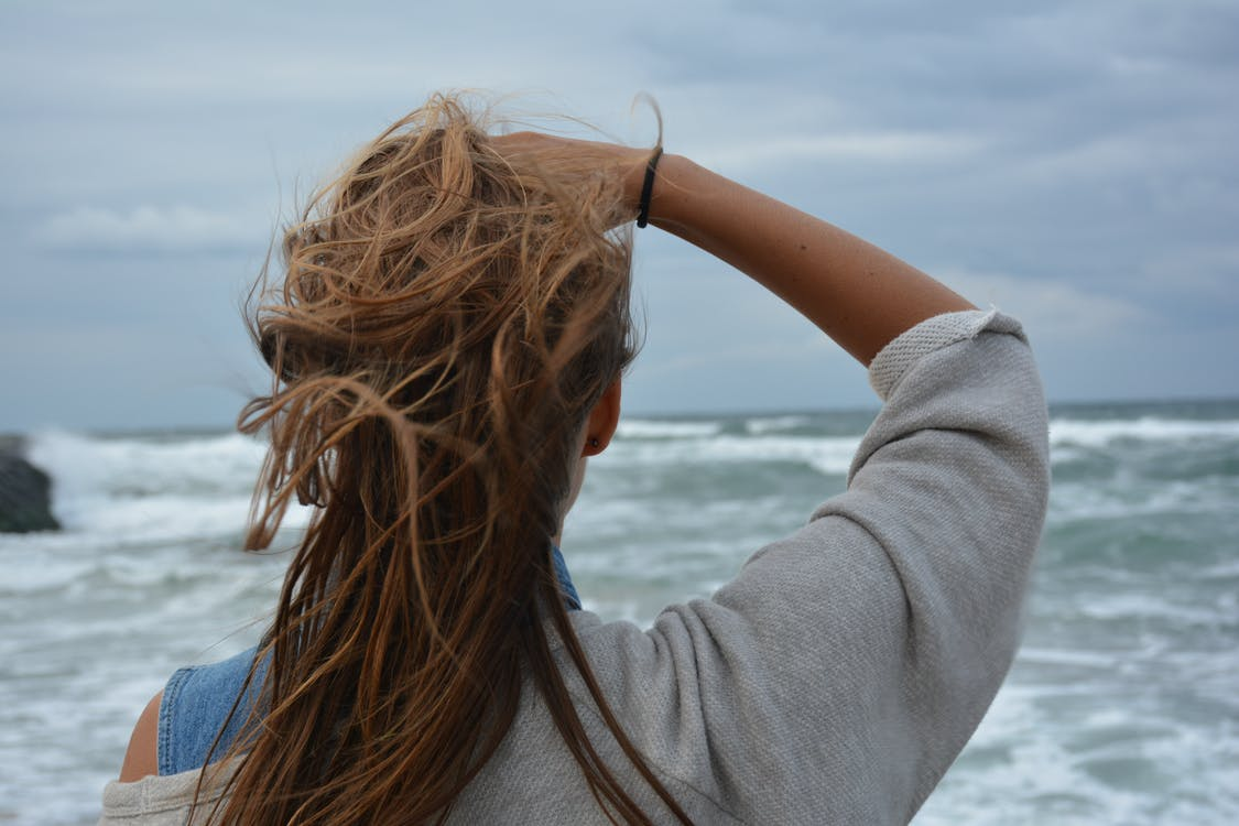 Woman Facing the Ocean during Day