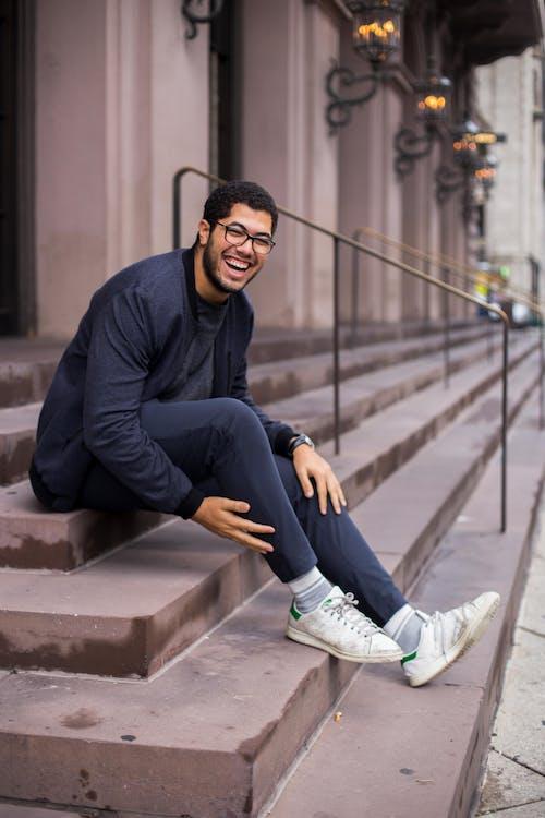 Mann, Der Auf Der Treppe Sitzt, Während Er Lächelt