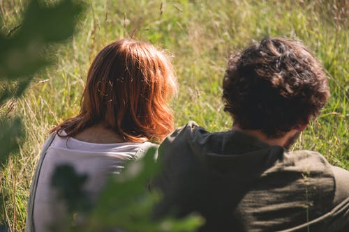 People Photography of Man and Woman Sitting on Green Grass Field