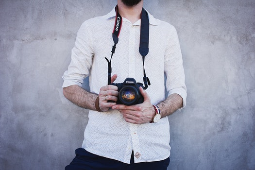 Man Wearing White Long Sleeves Holding Black Canon Dslr Camera