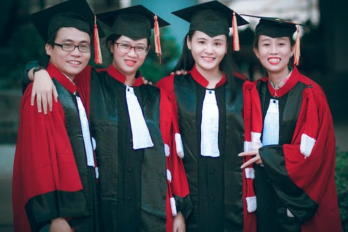Man and Women Wearing Red-and-black Academic Gowns and Black Mortar Boards