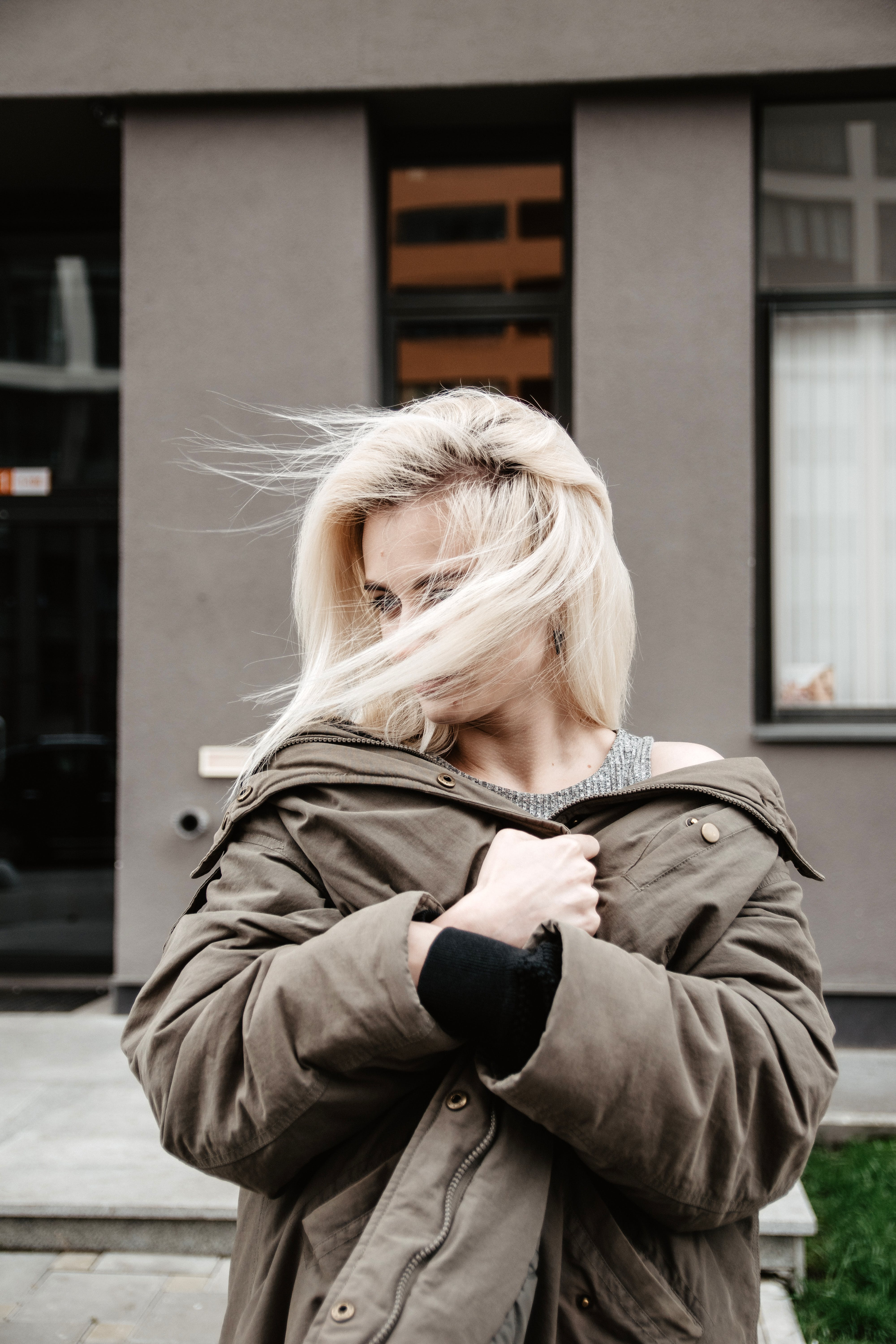 Photo of Standing Woman Wearing Brown Coat with Her Hair Covering Her Face