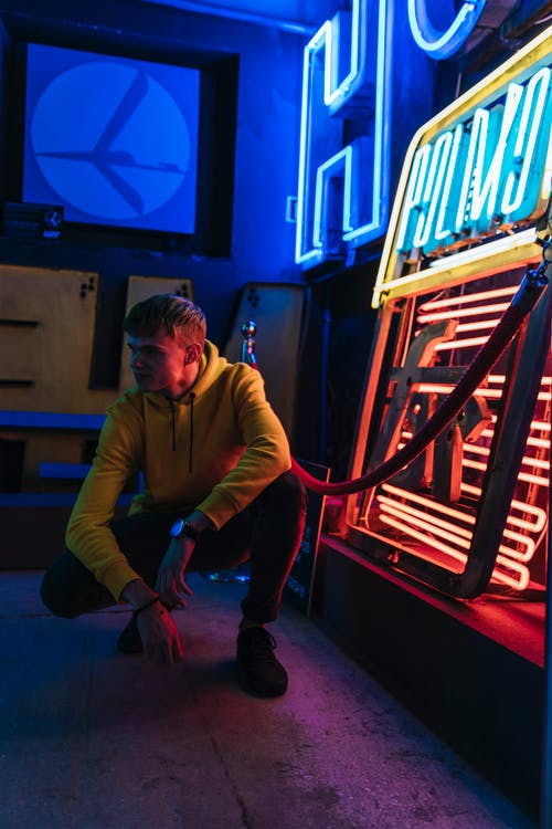 Photo of Man Squatting Beside Neon Sign