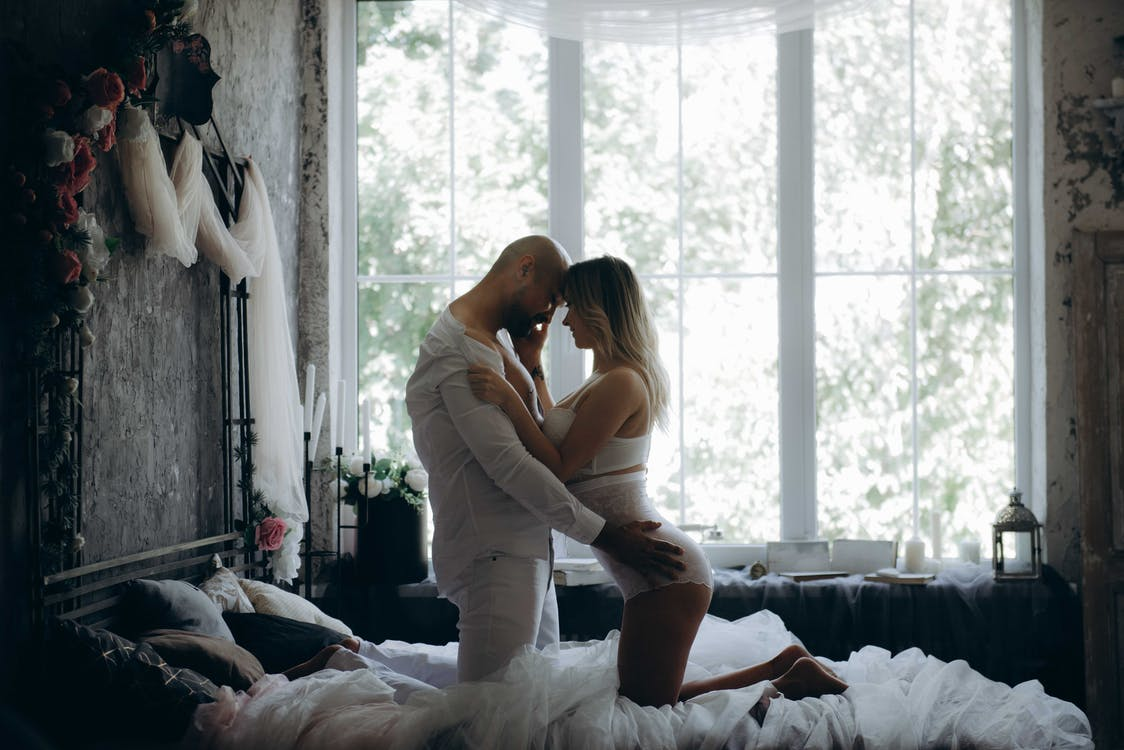 Man and Woman Kneeling on Bed Beside Window