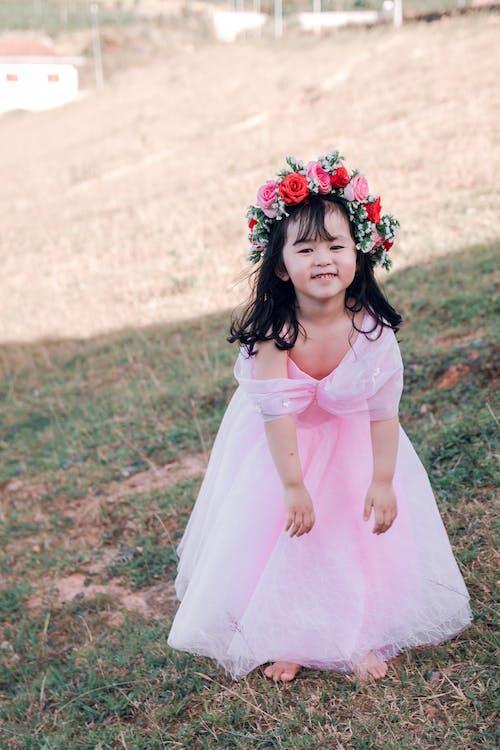 Girl With Pink Flowers Headdress Standing on Grass Field