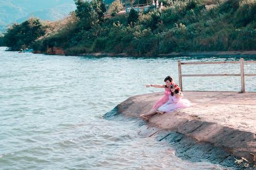 Woman And Girl Sitting Near Sea