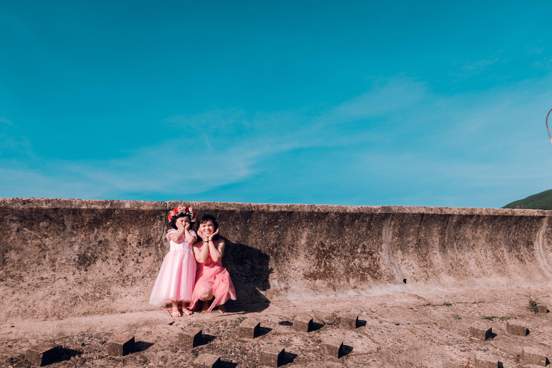 Two Girls Standing Near Grey Concrete Wall