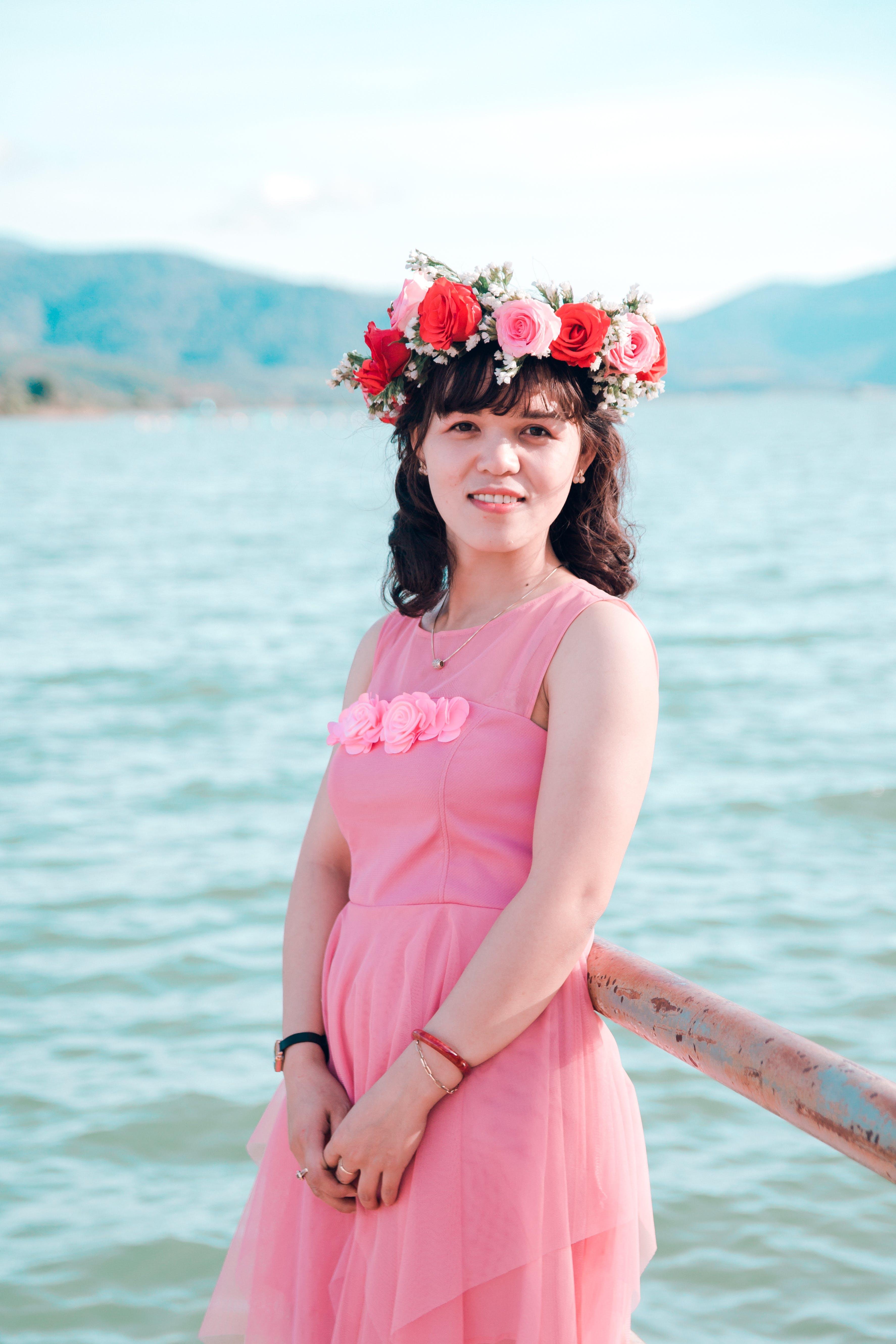 Woman in Pink Dress and Wearing Headdress Near Body of Water