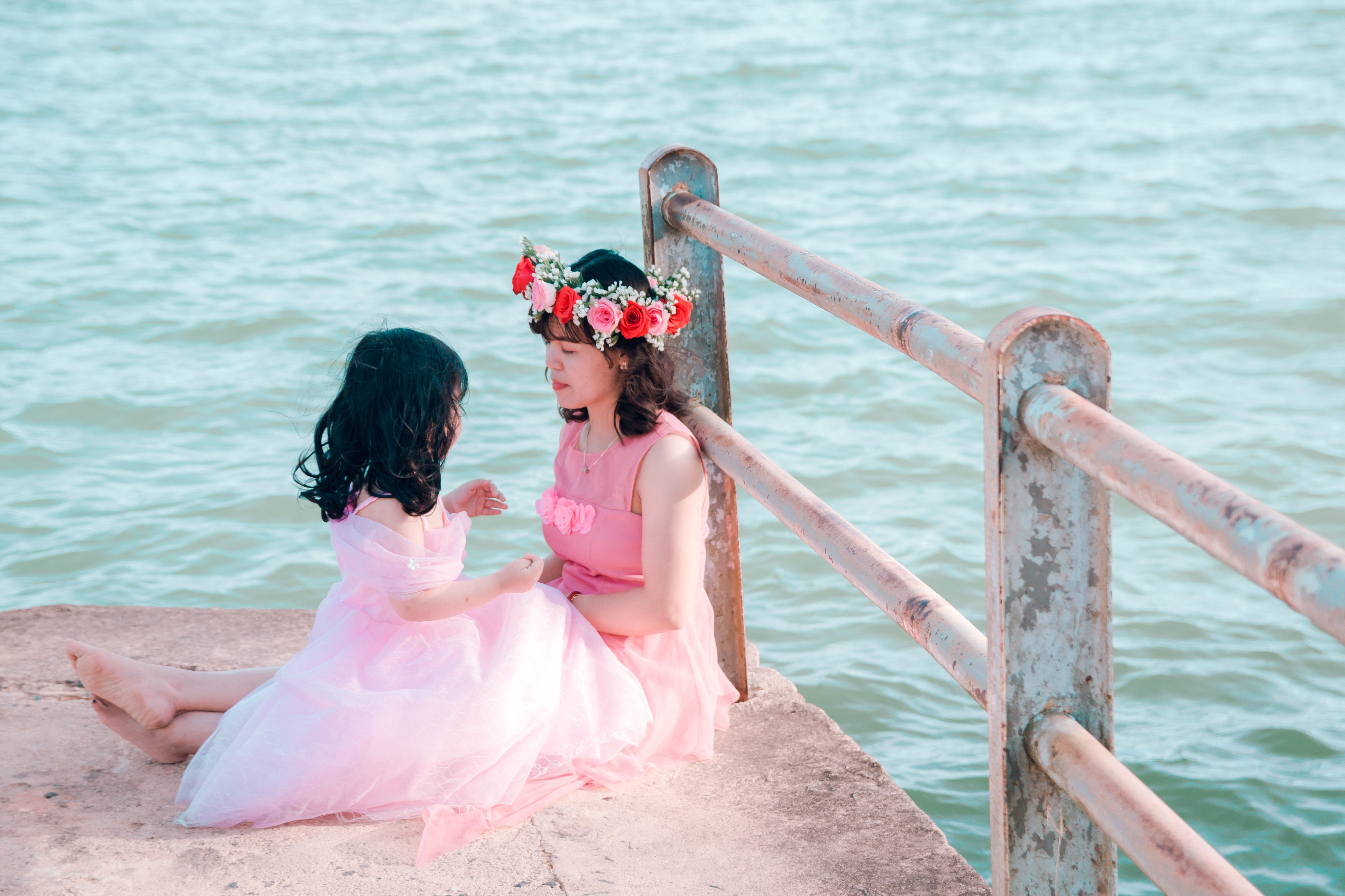 Woman And Girl In Pink Dress Sitting Near Body Of Water