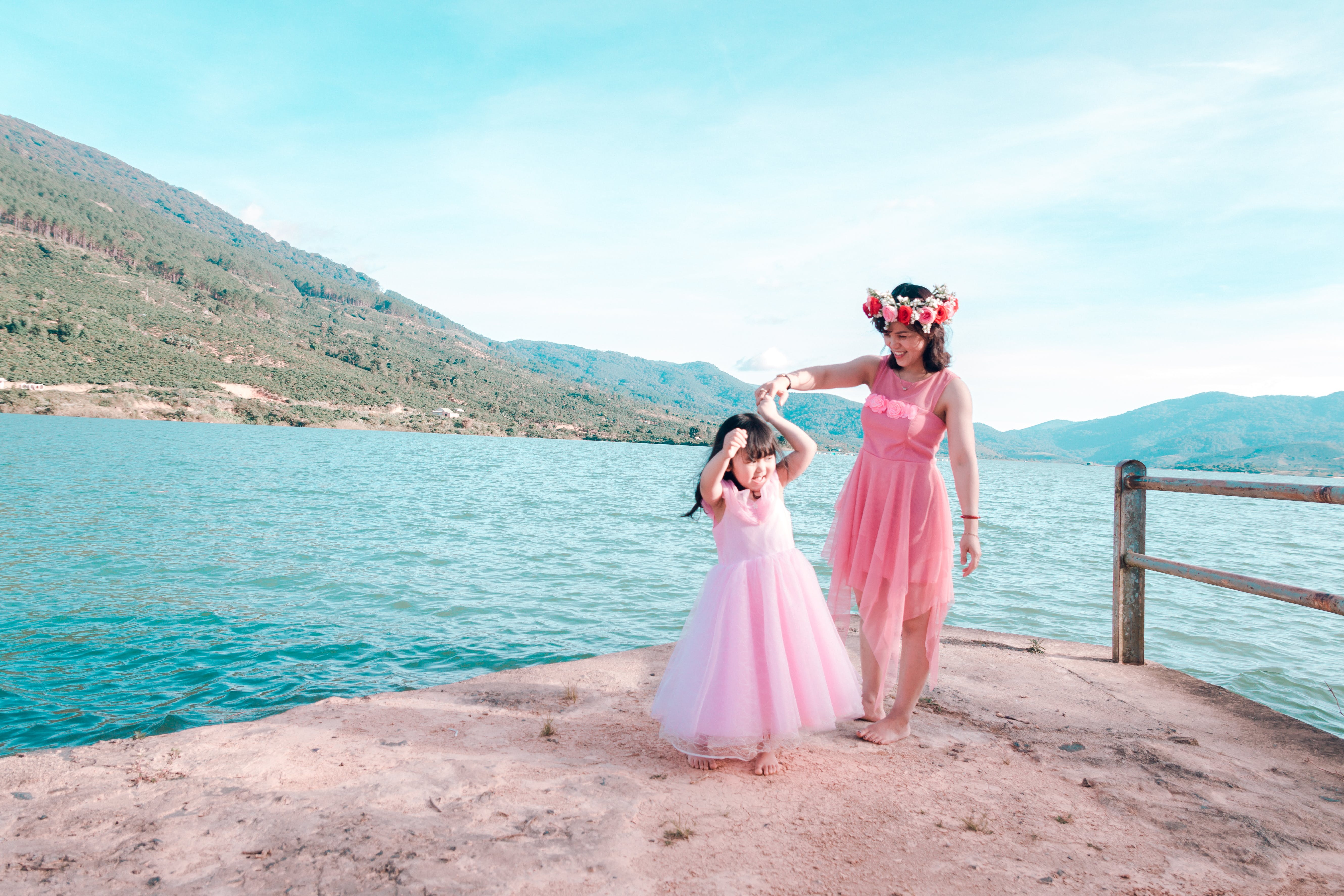 Woman and Child Wearing Pink Gowns Near Sea