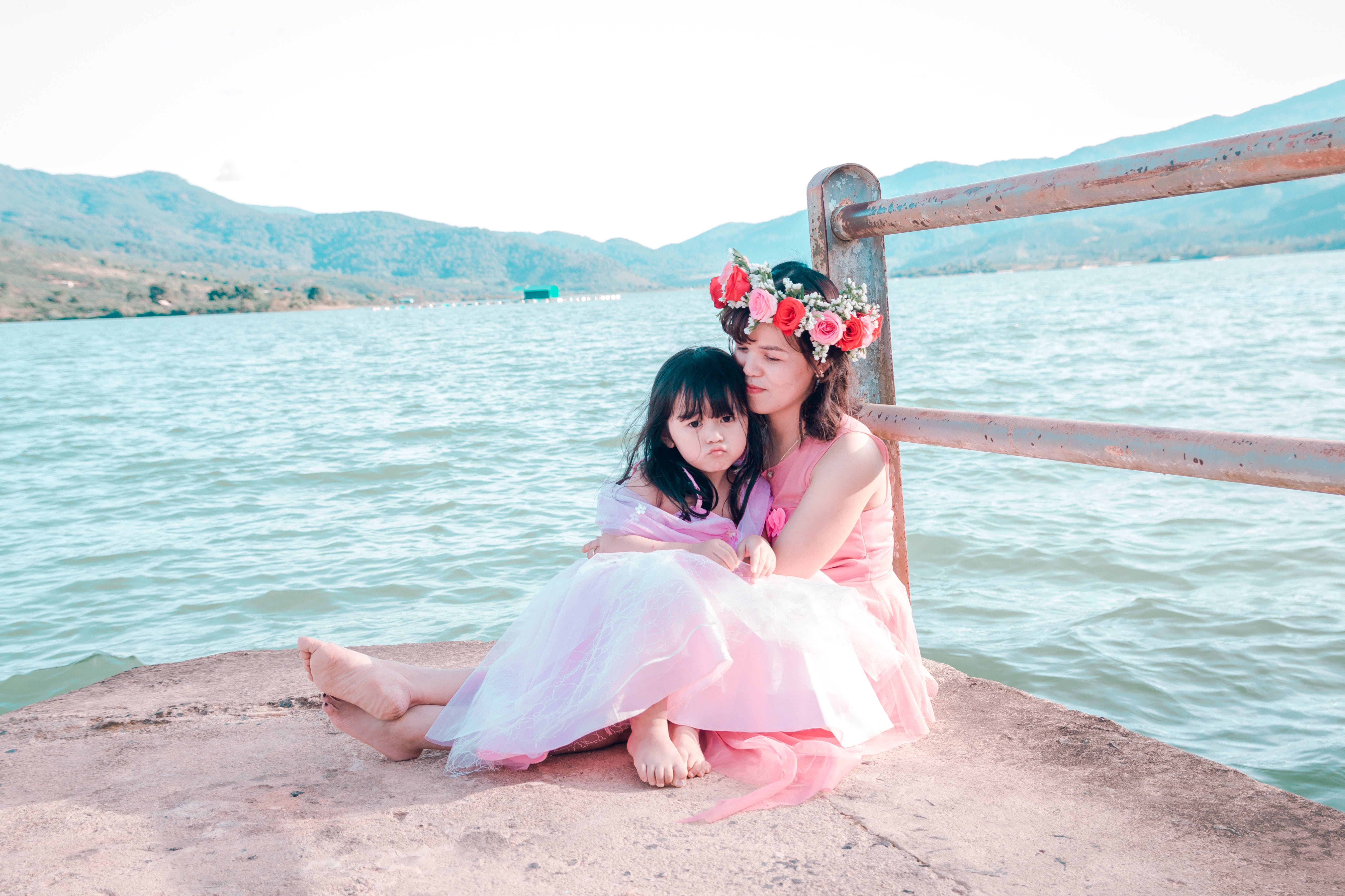 Woman And Girl Sitting Beside Body Of Water