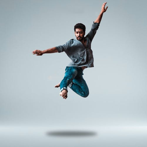 Man Jumping While Raising His Both Arms
