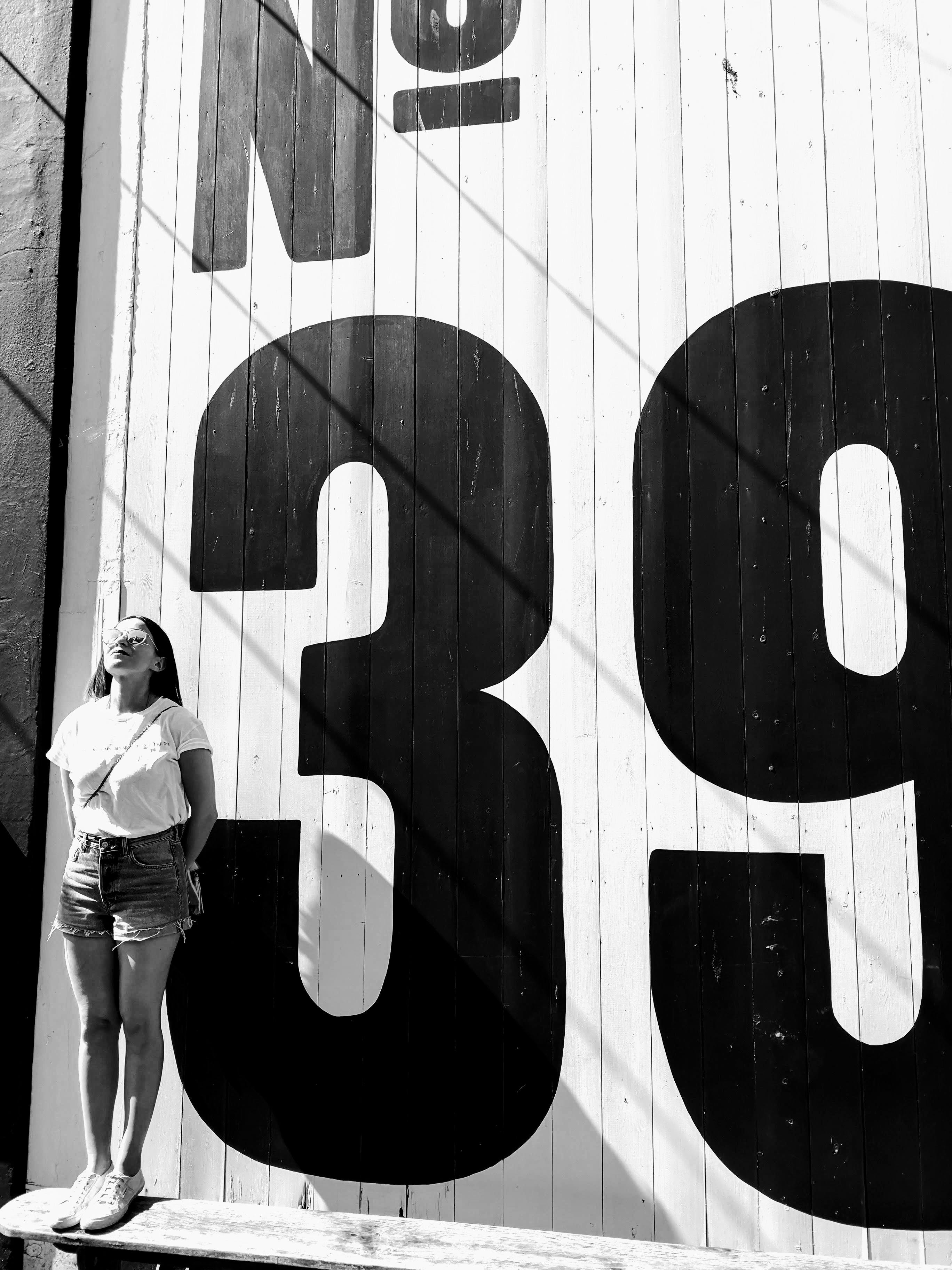 Grayscale Photo Of Woman Standing Beside White And Black Wall