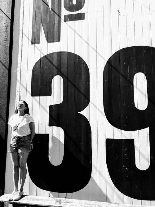 Kostenloses Stock Foto zu frau, mauer, person, schwarz und weiß
