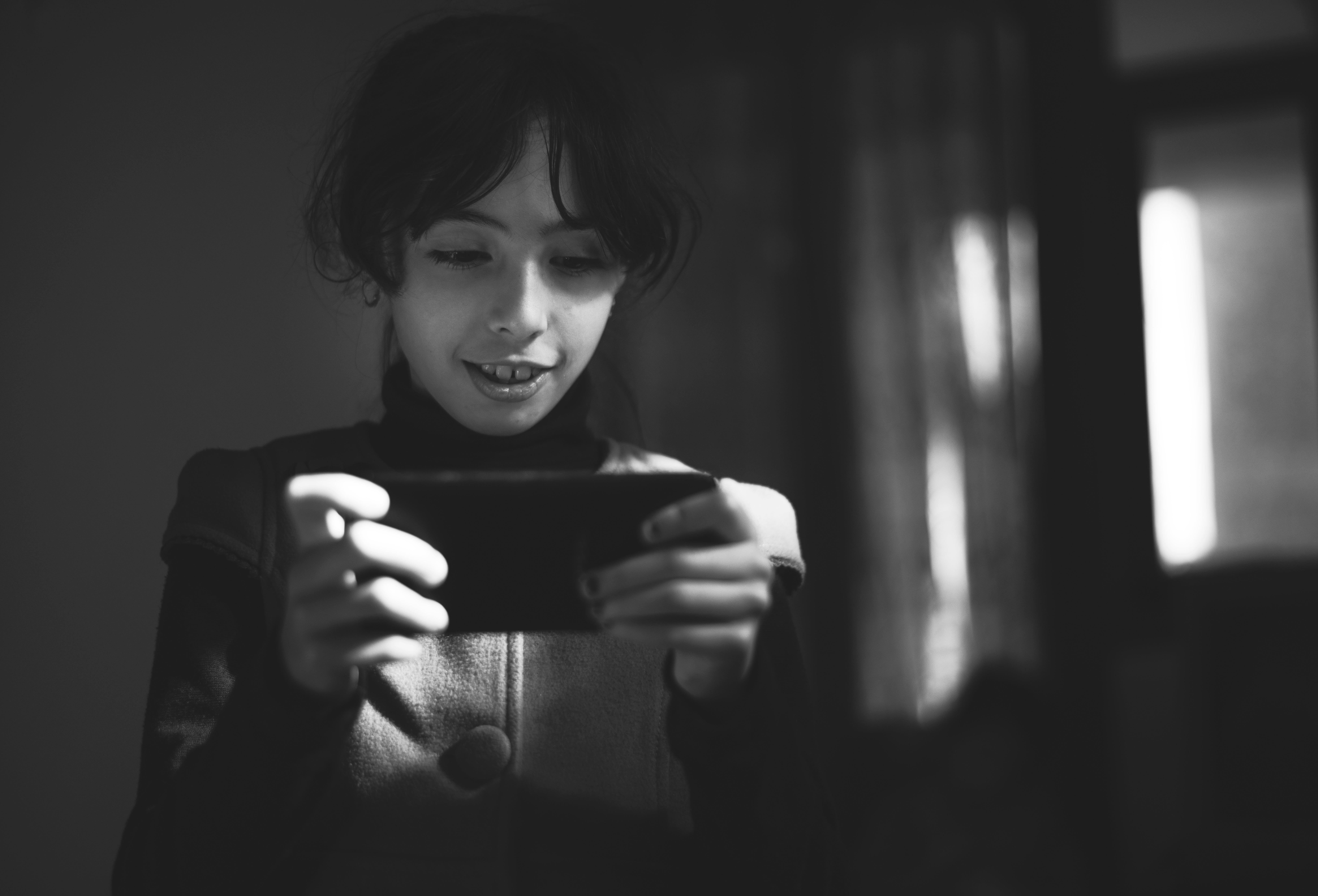 Grayscale Photography of Girl Using Smartphone