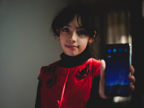 Girl Wearing Red and Black Top Holding Smartphone
