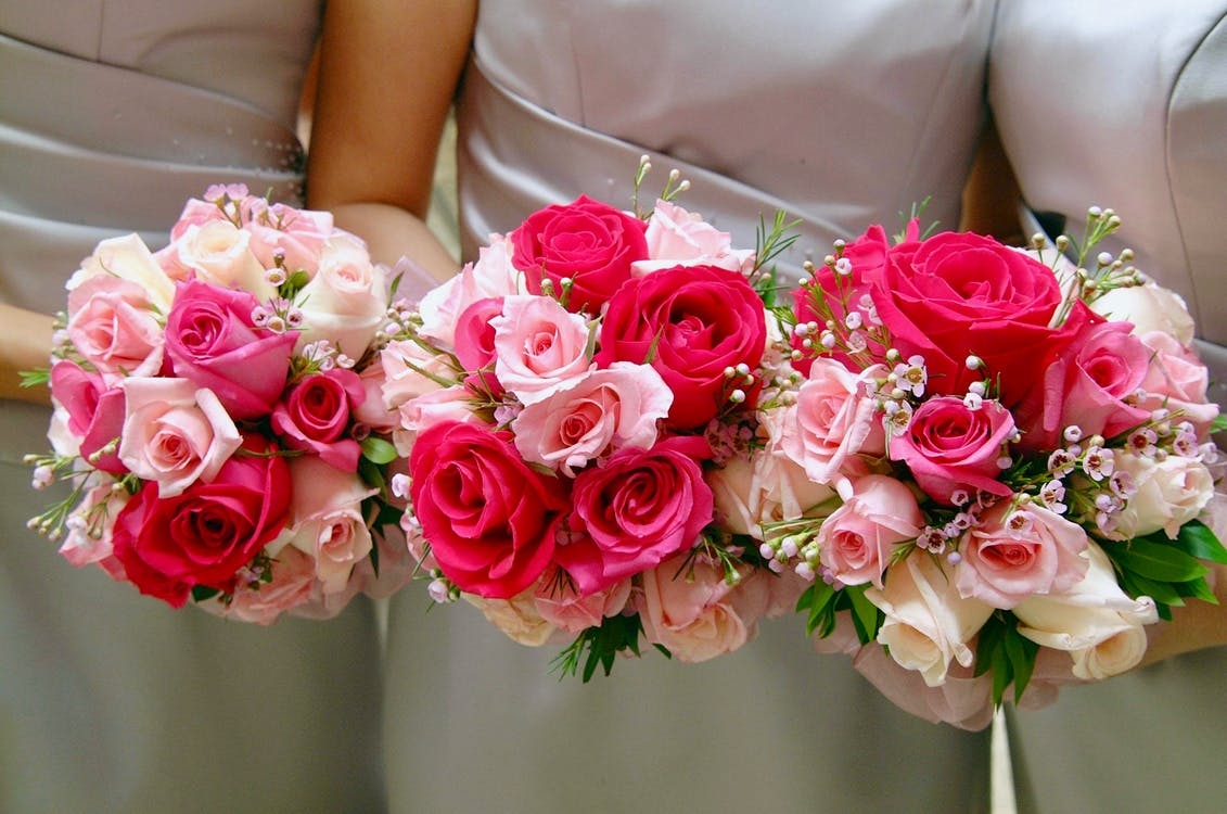 Three Women Holding Bouquet of Pink and Red Hybrid Tea Roses