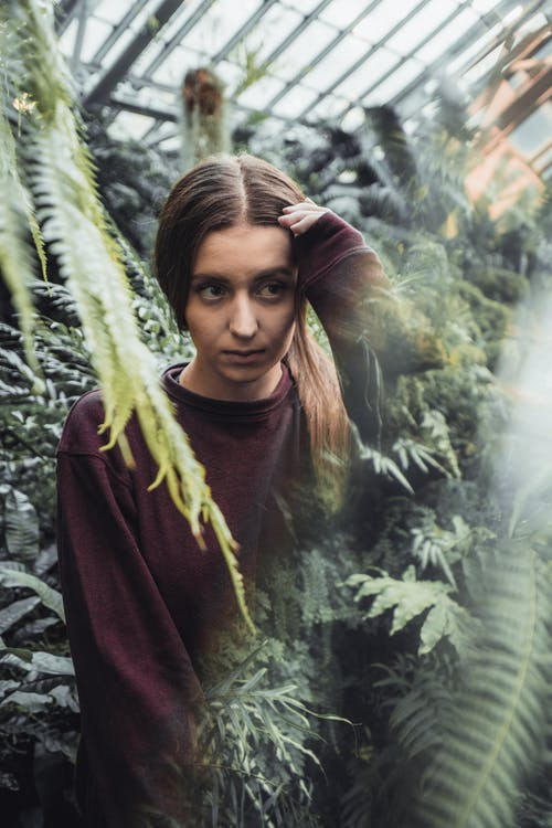 Woman Standing in the Middle of Fern Plants