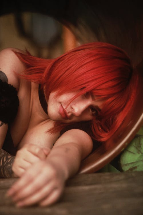 Red-haired Woman Lying on Brown Surface