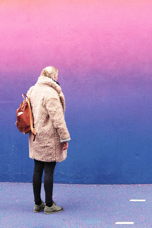 Woman Standing in Front of Pink and Blue Wall