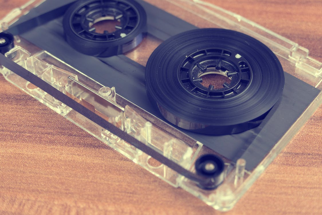 Clear and Black Cassette Tape on Brown Wooden Surface