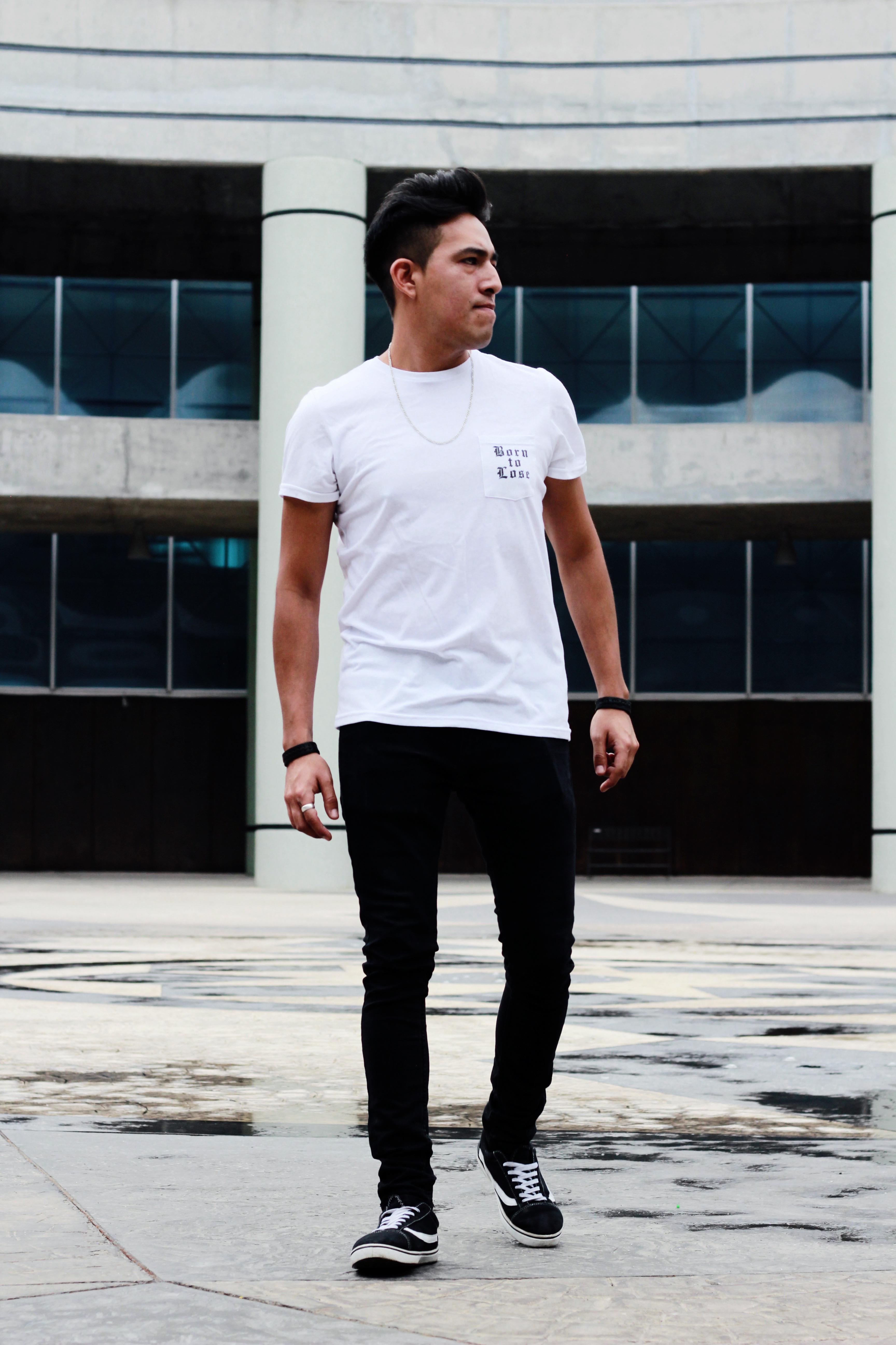 Man Standing Near Gray Building